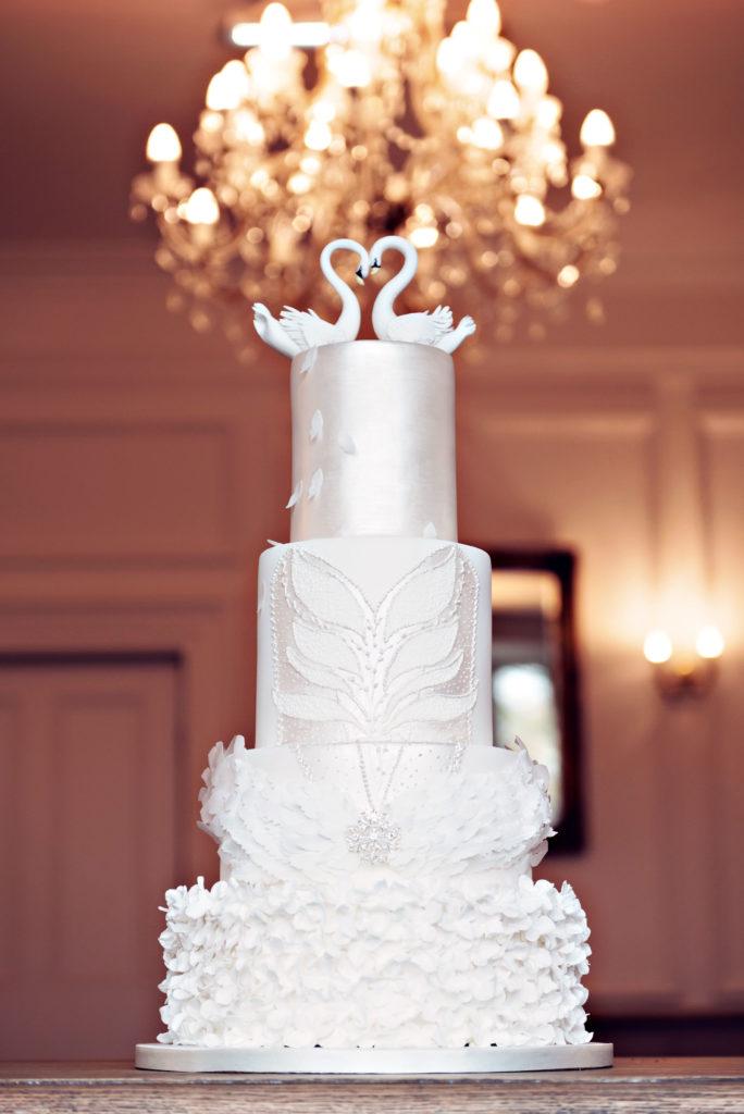 Photograph showing an elegant wedding cake inspired by Swan Lake the ballet