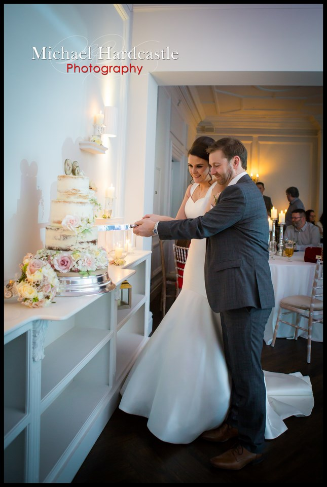 Full length picture of Bride and groom cutting the cake