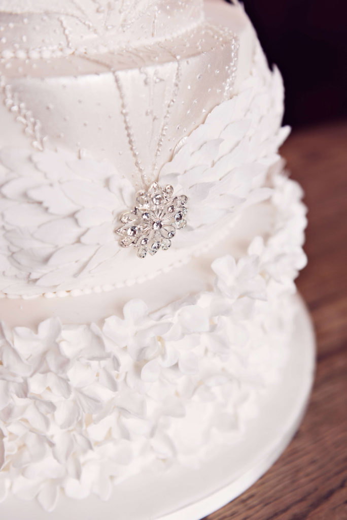 Luxury wedding cake with sugar flowers and sugar feather headdress
