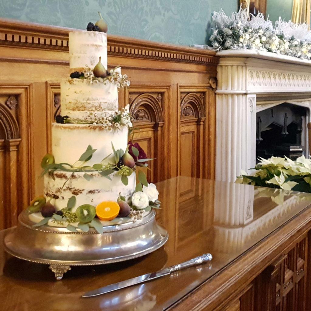 Semi Naked wedding cake dressed with fresh fruit and foliage