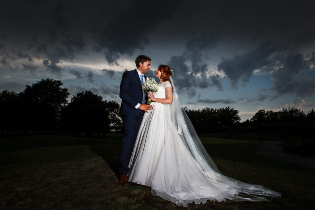 Bride and groom against dramatic thunder clouds