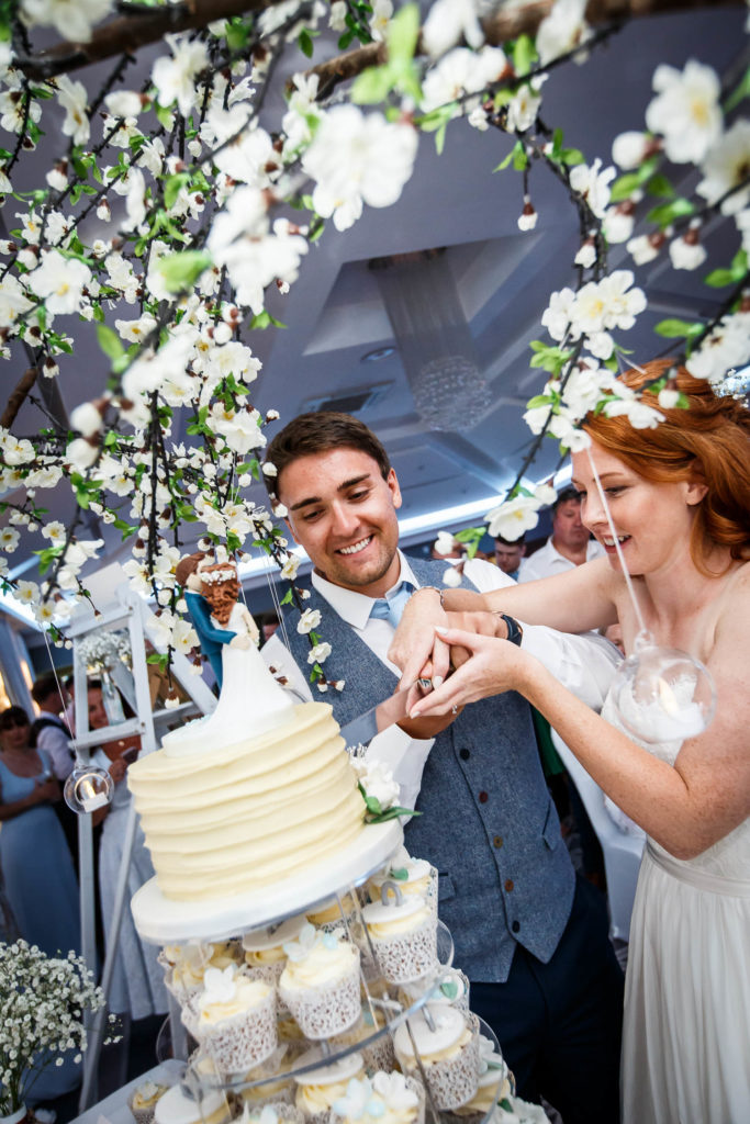 Bride and groom cutting the cupcake tower top cake surrounded by apple blossom