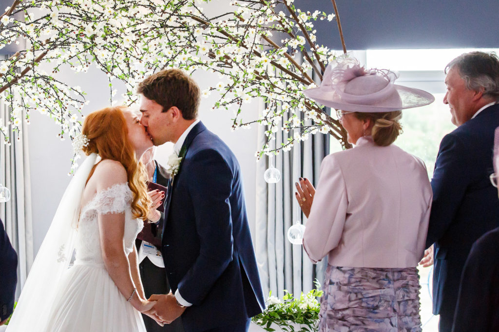 Bride and groom kissing surrounded by apple blossom