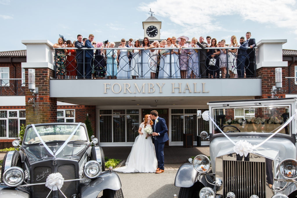 Bride and groom pictured at Formby Hall with guests on the balcony