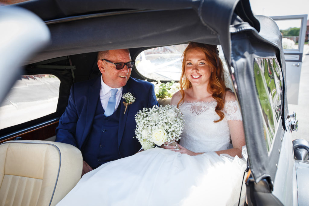 Bride with long red hair arriving with step dad in a vintage car