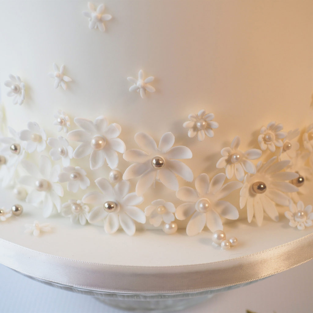 Contemporary white sugar flowers on wedding cake