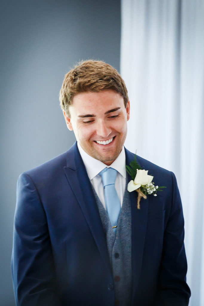 Groom in navy blue suit with white button hole