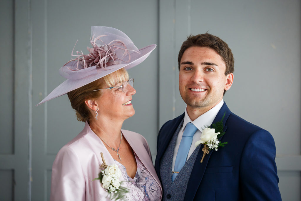 Groom with mother of the groom ivory rose and gypsophila button hole