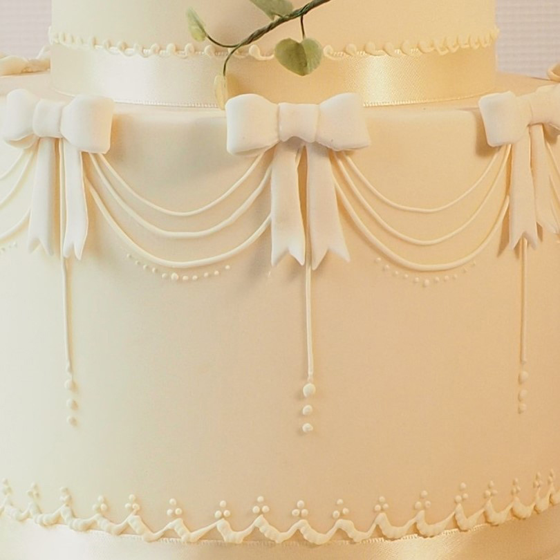 Royal icing detail on ivory cake, swags and bows