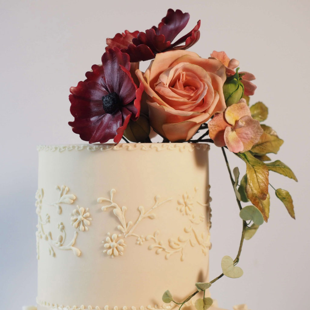 Top tier ivory wedding cake with hand piped royal icing and sugar flowers