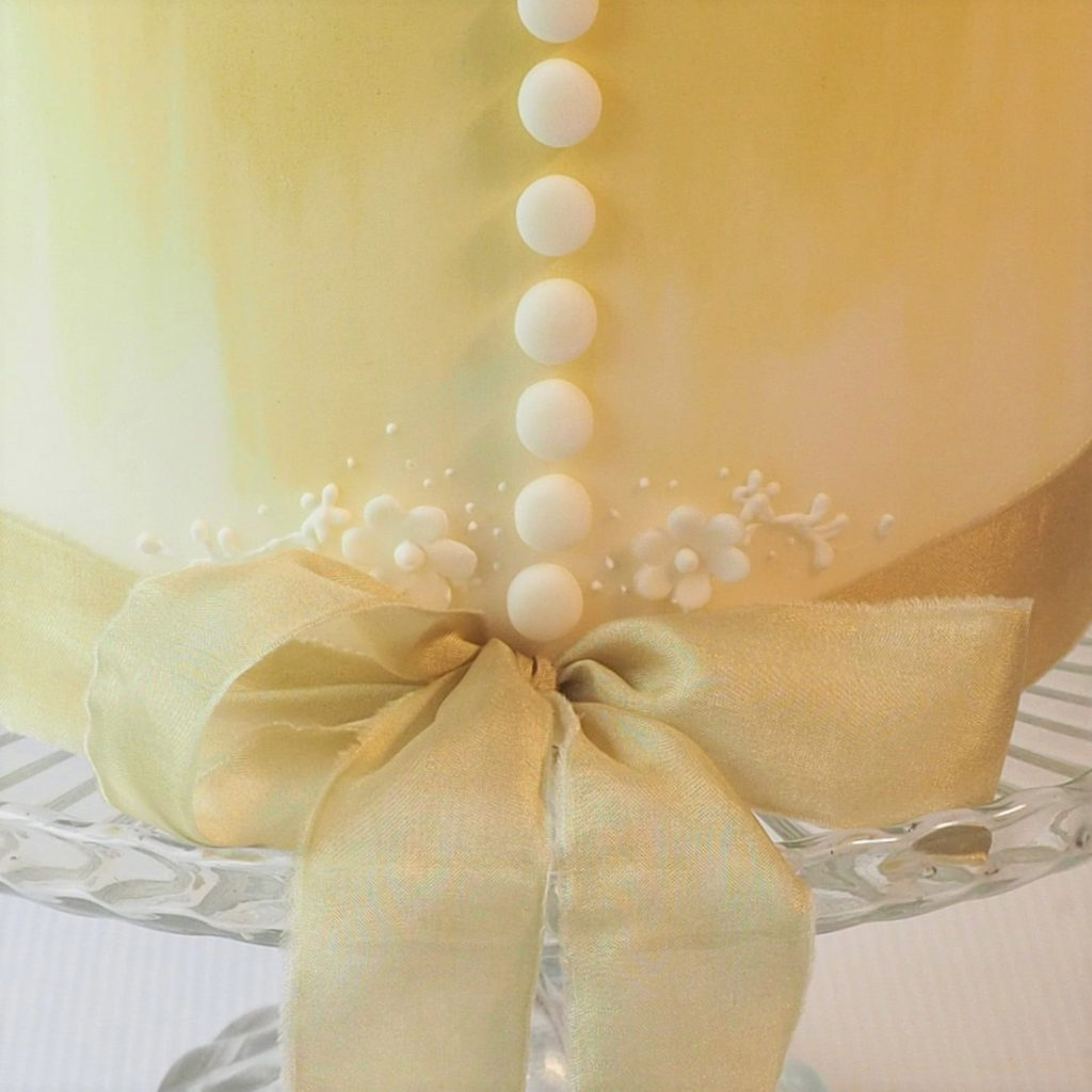 Close up of sugar button and bow detail on wedding cake