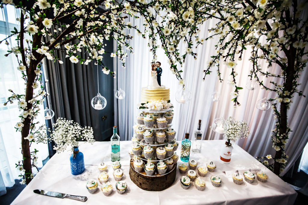 Cupcake tower surrounded by gin bottles top cake with couple bride and groom wedding cake topper