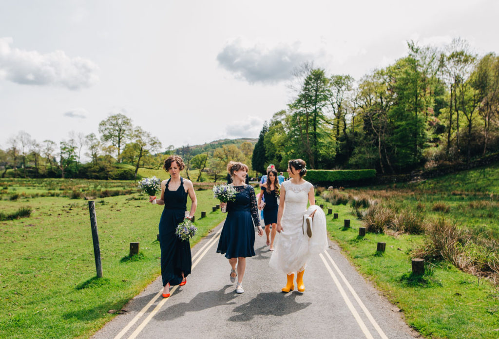 Bride and bridesmaids walking to the wedding venue. Bride in yellow wellington boots