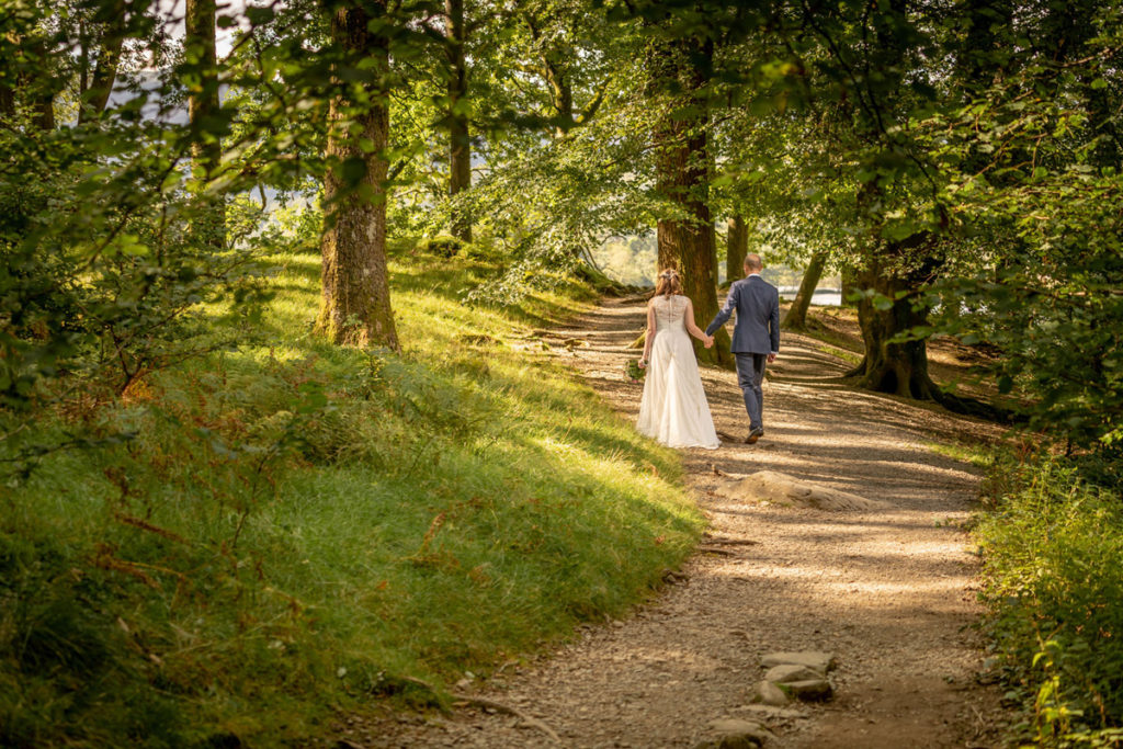 Bride and groom strolling in the woods at Cote How