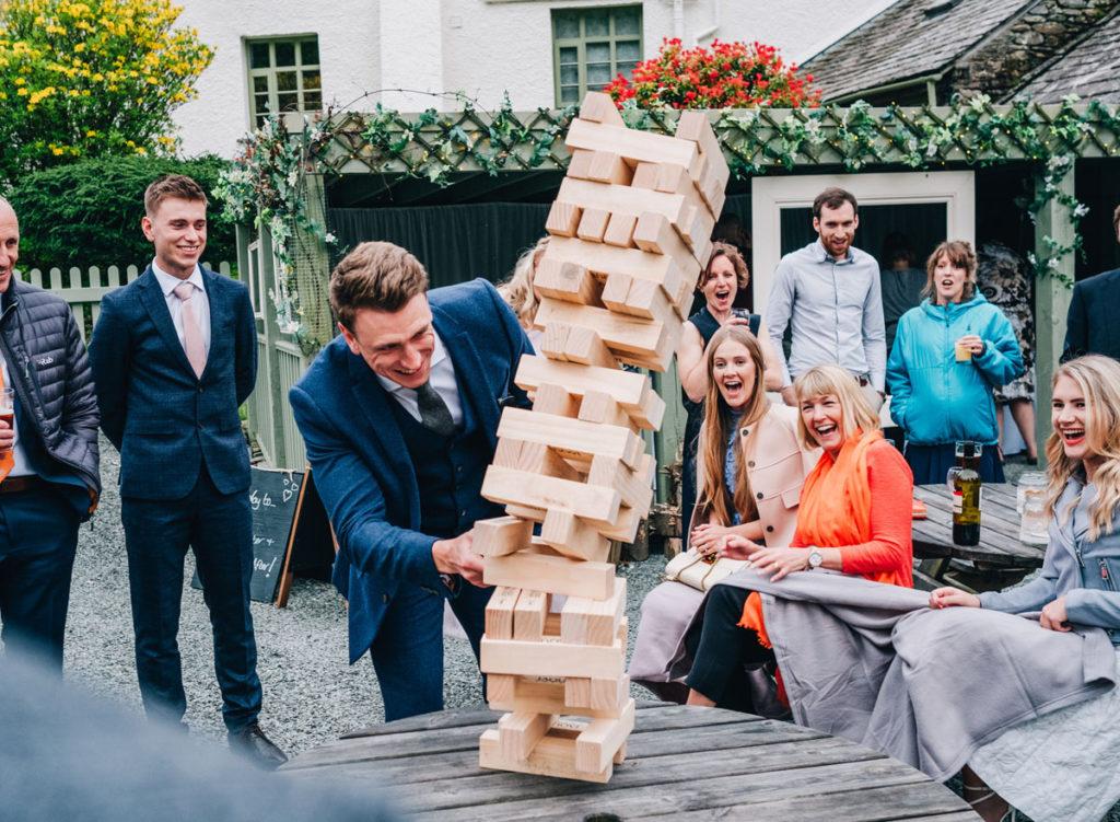 Groom and wedding guests having fun playing Jenga