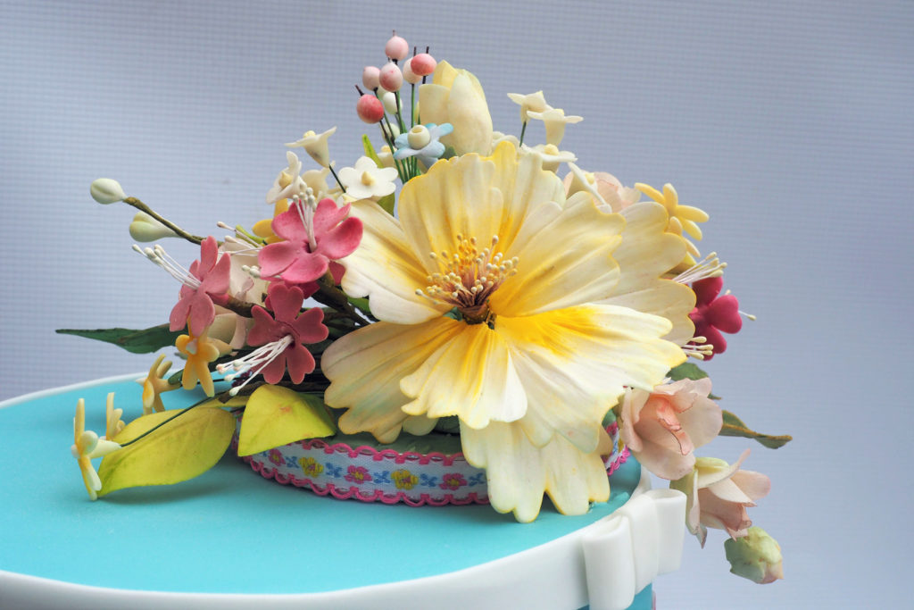 Pretty sugar flowers on an individual ribbon trimmed cake board